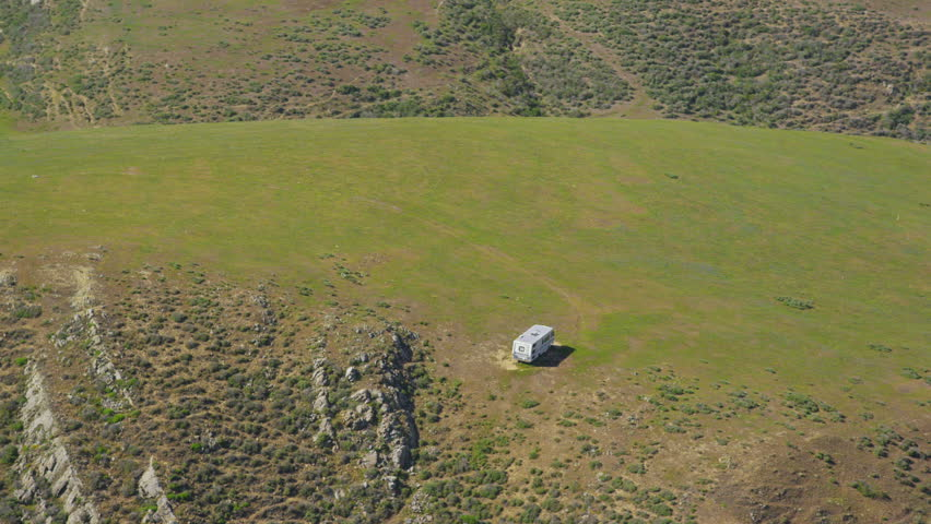 Aerial view of Motor Home on California Coastal road.  Helicopter flying along Big Sur coast near San Francisco with the Pacific ocean and State park mountain range. - HD stock video clip