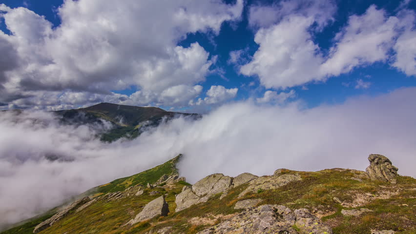Timelapse of beautiful summer landscape in mountains with clouds passing by against blue sky and misty fog falls on the ground. Shot near the peak of Pip Ivan mountain in Carpathians, Ukraine. - HD stock video clip