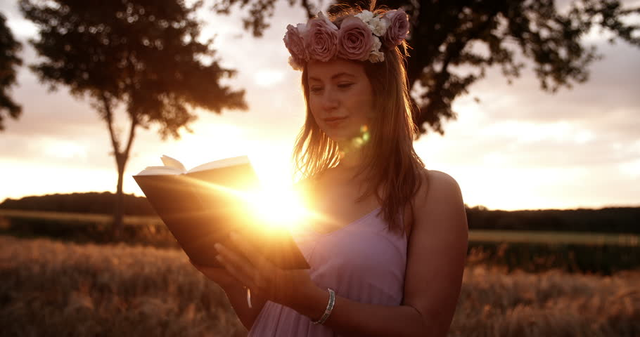 Girl with flower crown reading a book at sunset - 4K stock video clip