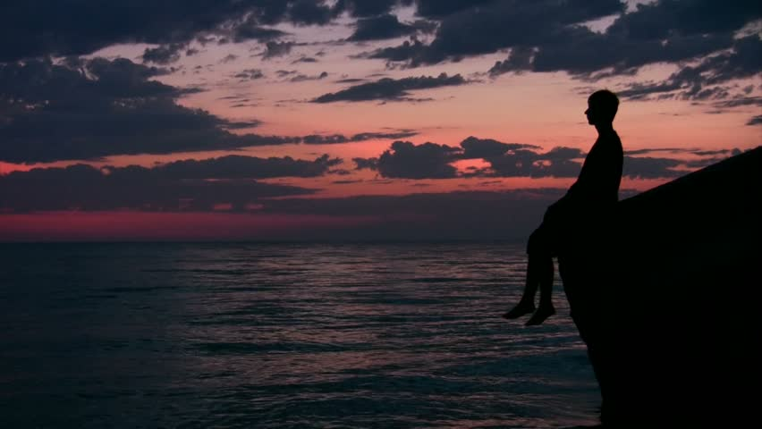 silhouette of youngster sitting against sunset sky and dangles legs  - HD stock video clip