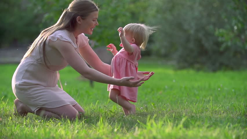 Adorable toddler hardly keeping balance in her first steps to mother | Shutterstock HD Video #7250107