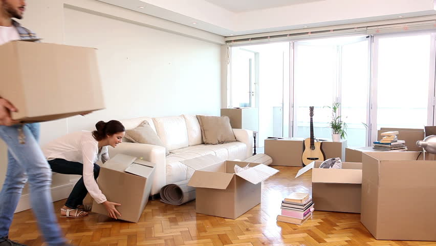 Attractive couple moving boxes into their living room in their new home