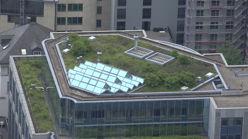 ULTRA HD 4K Aerial view of solar panel on the roof of skyscraper, residential building in metropolis city for electric power by day