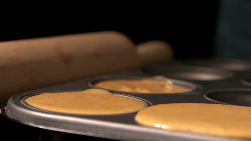 Chocolate square dropping into cupcake batter in tray in slow motion