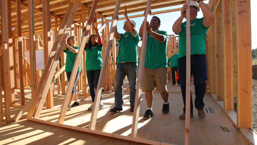 Volunteers working together lifting wall