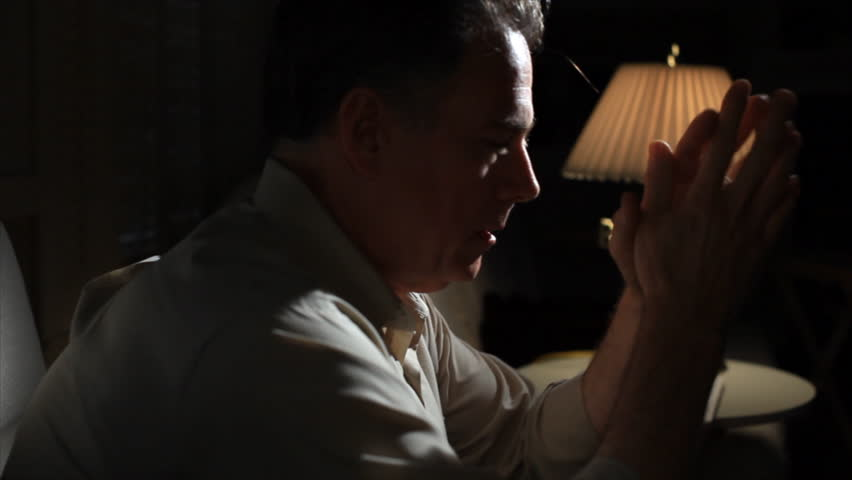 A man sitting in a dimly lit room, who appears worried. - HD stock footage clip