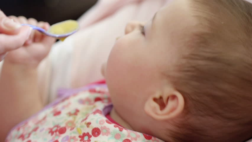 Mom feeding small baby girl close up - HD stock footage clip