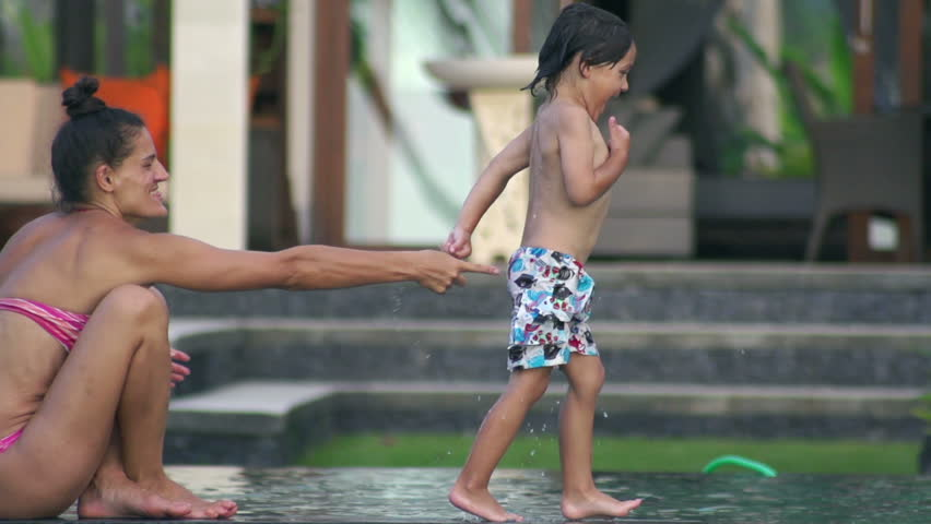 Boy jumping to the pool and diving, slow motion shot