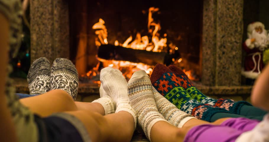 Feet in woolen socks warming by cozy fire in Christmas time in slow motion. Family with two kids warming their feet by the fireplace in winter time. Slow motion filmed at 120 fps 4k graded from RAW