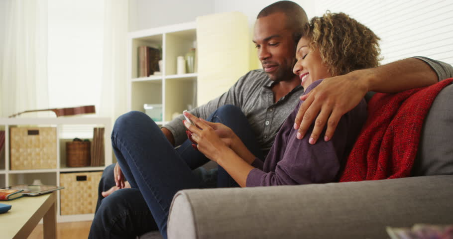 African American couple using devices on couch - 4K stock video clip