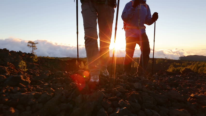Hiking shoes on hikers walking at sunset. Man and woman hiker hike boots in closeup while trekking with hiking poles. - HD stock footage clip