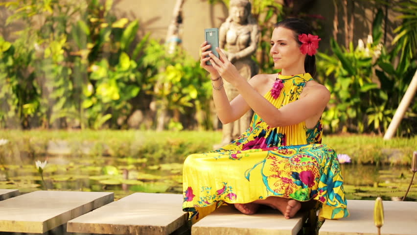Attractive woman taking photo with cellphone in exotic garden  - HD stock video clip