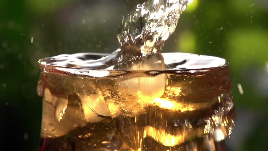 Whirling Ice Cubes in a Glass. In a glass of sparkling wine with a sweet swirl ice cubes close-up. Slow Motion at a rate of 240 fps - HD stock video clip