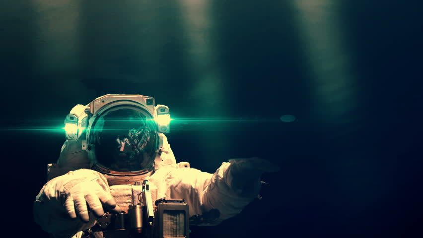 Astronaut lit from above by lights from the International Space Station