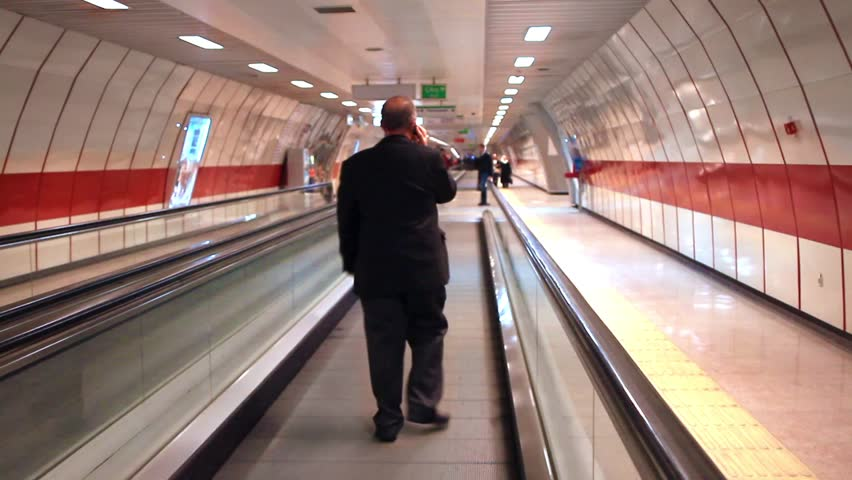 ISTANBUL - FEB 7, 2013: Metro line is one of the newest public transportation system operating since 2000. Commuters walk on the walkway at Taksim Levent underground. Man walking and talking by phone.