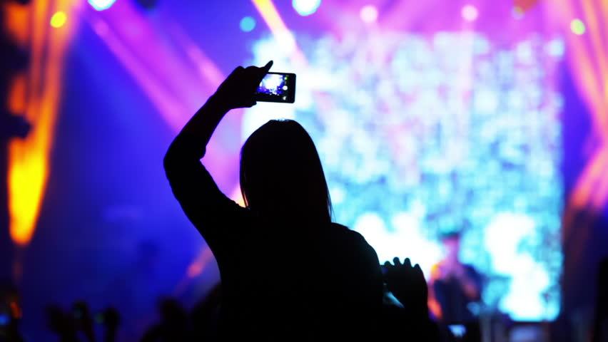 Rock concert in night club. People on the scene without focus. Girl records video of musicians on her smartphone. Silhouette