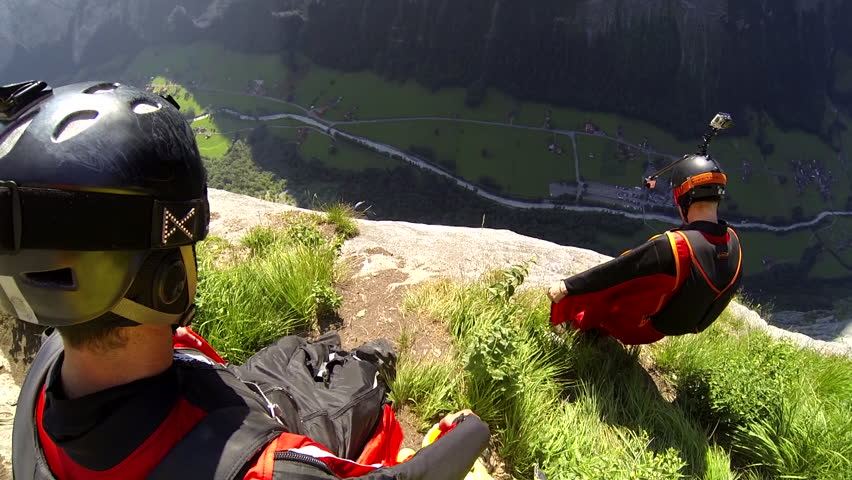 Two base jumpers in wingsuits jumping from a cliff, gliding down over a green landscape, POV