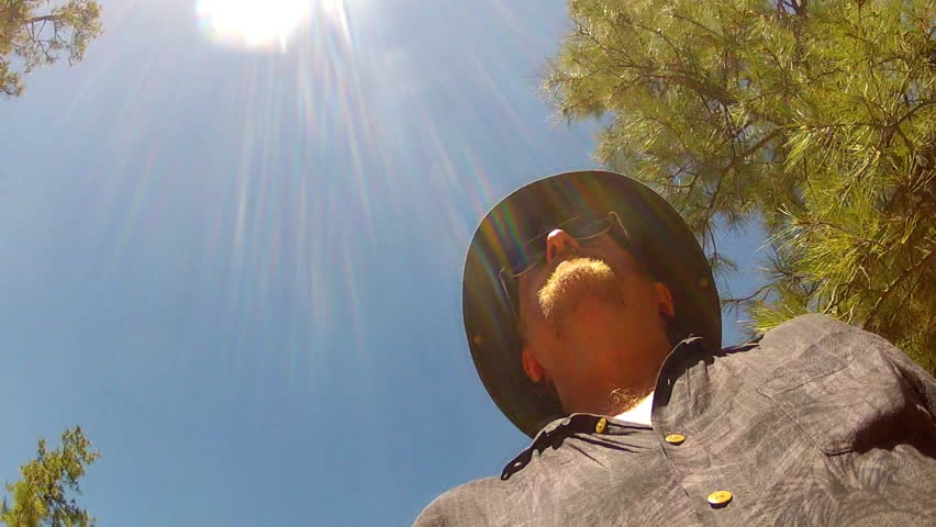 FLAGSTAFF, AZ/USA: Sept. 7, 2014- A low angle shot of a man or ranger walking in the forest under tall trees circa 2014 in Flagstaff.  - HD stock video clip