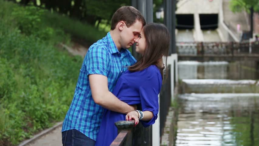 Young man leans over woman and kisses her near small river in park at summer day