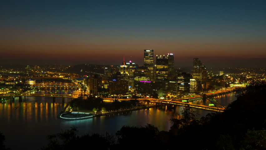 (Time-lapse/Zoom-in) Morning twilight transitions to sunrise over Pittsburgh, Pennsylvania including the skyline, bridges and Point State Park at the confluence of the Allegheny and Monongahela Rivers - 4K stock footage clip