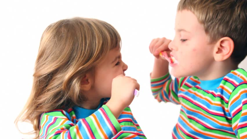 boy and girl brush teeth looking against each other, then turn and smile  - HD stock video clip