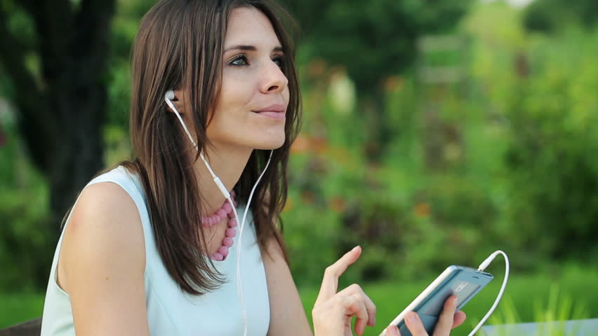 young beautiful businesswoman listening to the music in the garden  - HD stock video clip