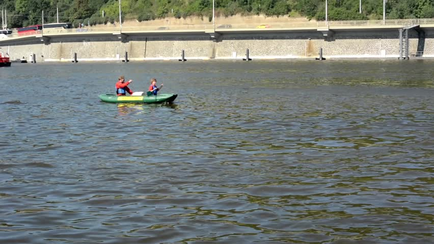 people on board and paddling - canoeing - boats on the river (Vltava) - city (buildings) in background - bridge - sunny - HD stock video clip