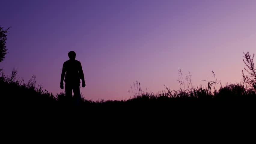 traveller with rucksack walks from camera against sunset summer sky