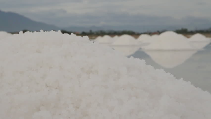 Piles of salt in both for ground and background. The water reflects their image until the camera pulls out of focus