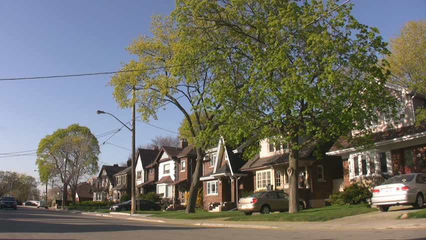 Spring street. Spring street scene with big green tree. Houses in the suburb of East York, Toronto, Ontario, Canada.  - HD stock footage clip