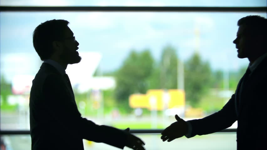 Outlines of two businessmen shaking hands near the window