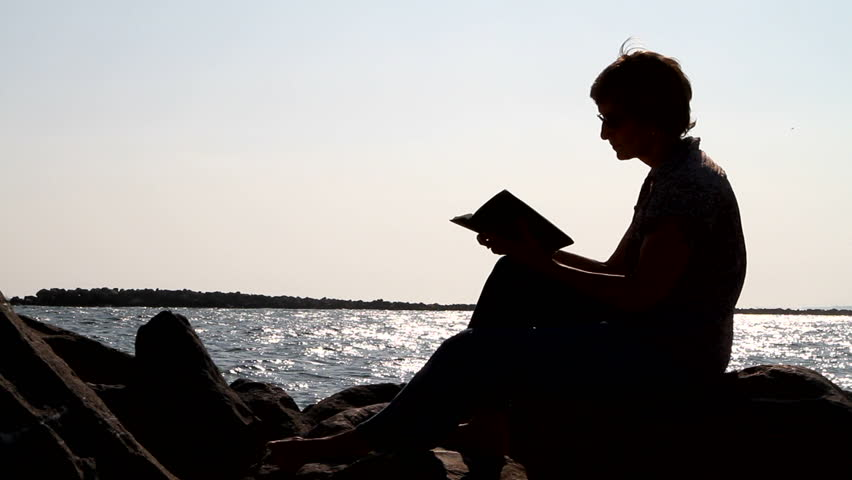 Silhouette of woman sitting on a rock studying the bible by a body of water. - HD stock video clip