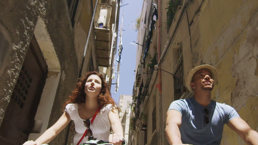 Attractive couple cycling in small Italian town and having fun