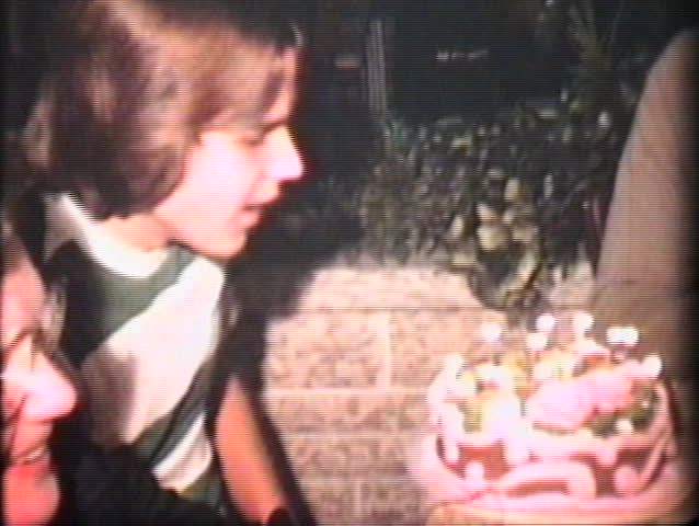 A teenage boy blows out the candles on his unusually pink birthday cake. - SD stock video clip