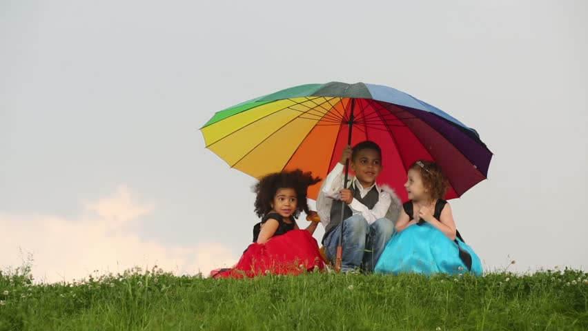 Three children sit on grass under colorful umbrella during rain and laugh - HD stock video clip
