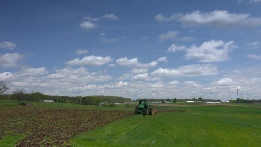 Driving by farmer plowing a field along a back country road. Early spring. - HD stock footage clip