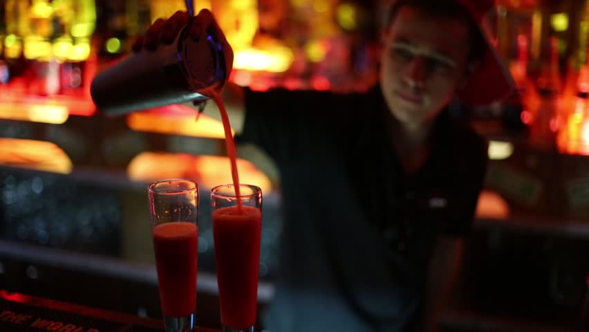 MOSCOW, RUSSIA - MAR 8, 2013: Barman mixes cocktail in bar Theme. In Theme bar bartenders prepare variety of cocktails and DJs play music - HD stock video clip
