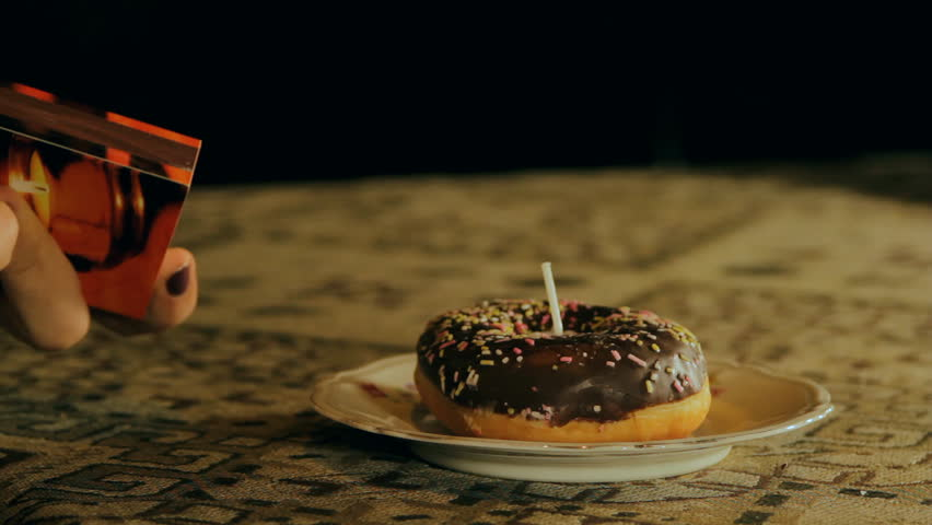Hands Lighting Up A Birthday Candle In A Doughnut Side Shot | Shutterstock HD Video #7671244
