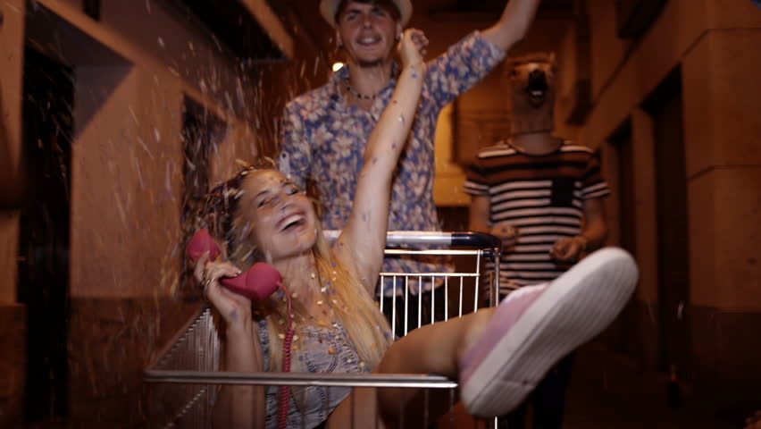 Friends being silly and partying with shopping cart and confetti in streets