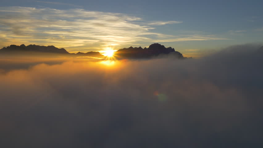 AERIAL: Beutiful golden sunset above the clouds