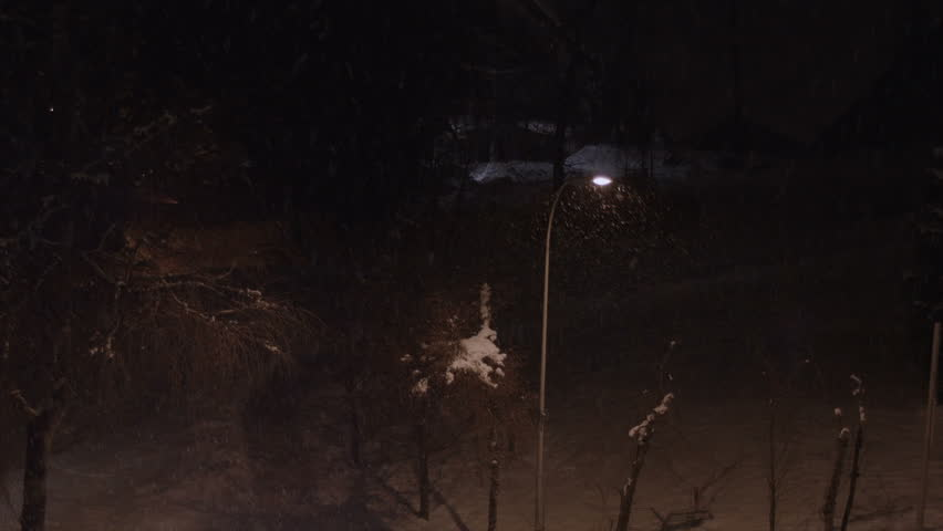Snowfall in a village by night, illuminated by streetlight - HD stock footage clip