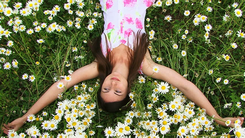 Girl on the field chamomile. A beautiful young girl lying on a beautiful chamomile field.  - HD stock footage clip