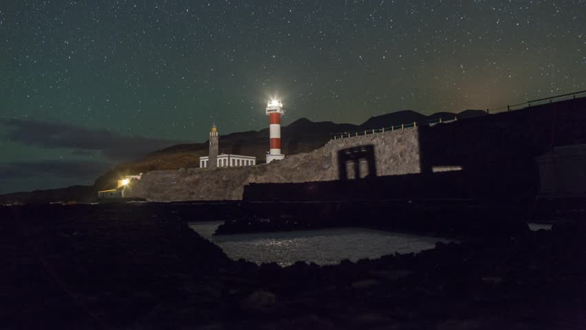 Lighthouse at Fuencaliente, La Palma, with salt pans, night sky timelapse footage with vertical dolly movement.