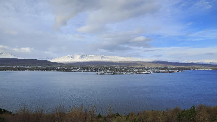 City of Akureyi, Iceland filmed from the Hringvedur (ring-road), route 1 with river and clouds, in autumn.