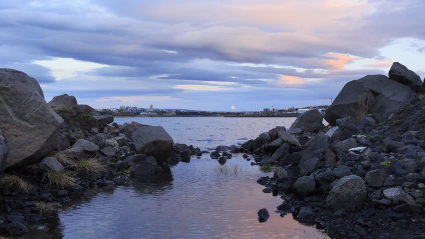Full moon rising over the city of Reykjavik, Iceland.  Timelapse footage.
