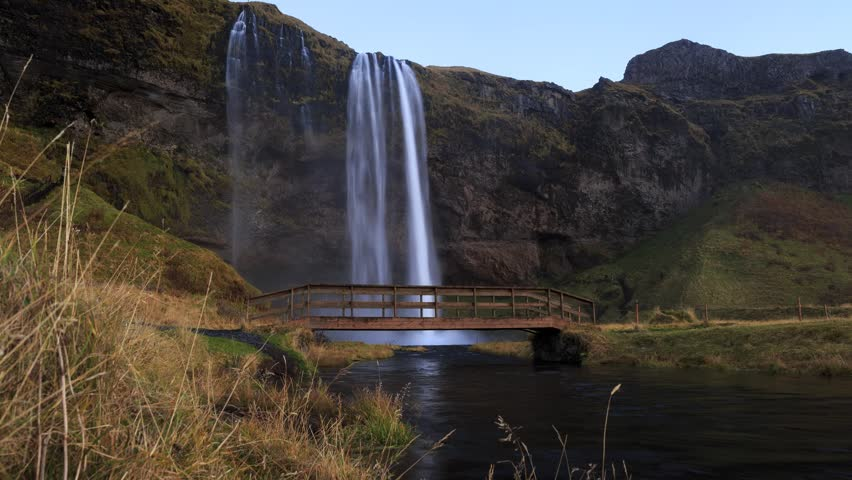 Seljalandfoss waterfall with walking bridge in southern Iceland. Timelapse footage with dolly movement.
