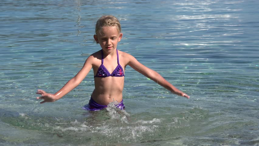 4K View of a Child Playing, Slashing Water in Mediterranean Sea Waves, Caucasian Blonde Happy Little Girl Dancing on Greece Beach, Coastline, Children in Summer Vacation - 4K stock footage clip