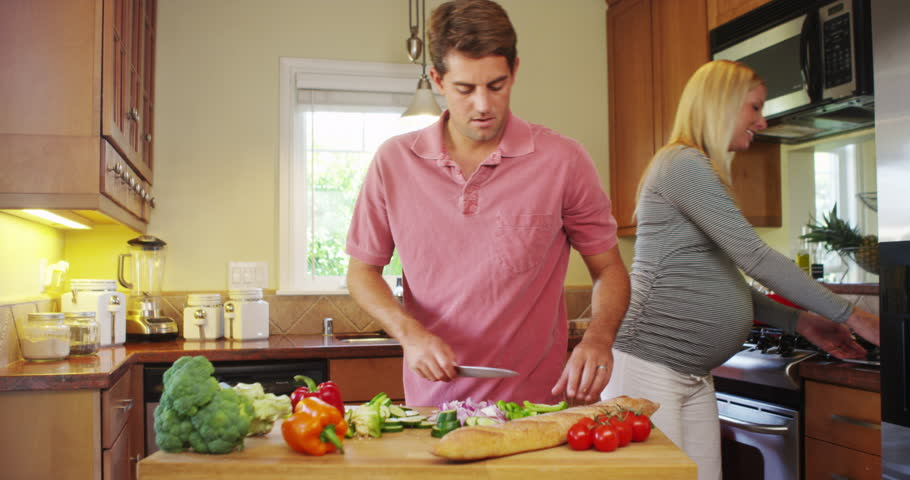 Happy pregnant couple working together in the kitchen - 4K stock footage clip