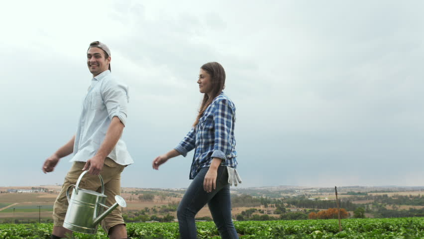 Young happy lifestyle farming couple carrying water can and inspecting produce before harvest.  - HD stock footage clip