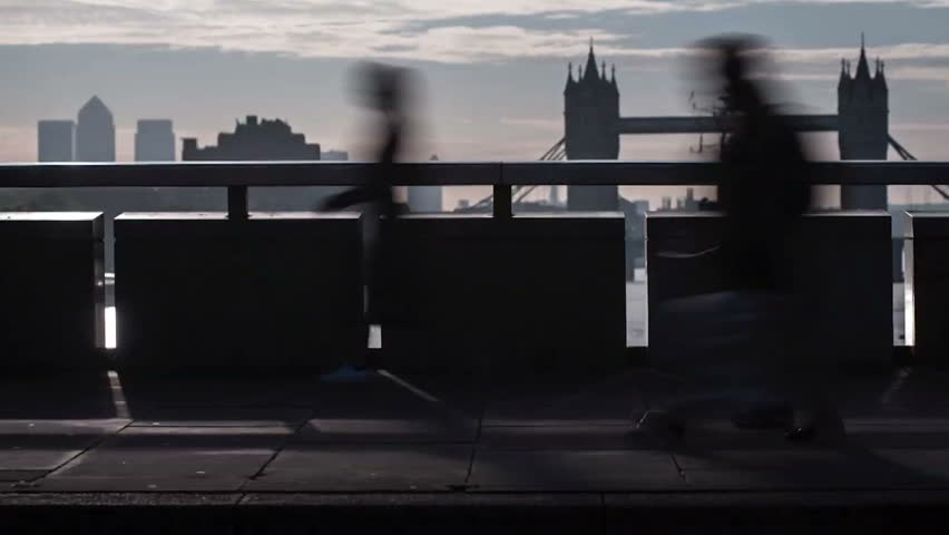 Timelapse of business commuters crossing London Bridge in London during the rush hour. Panning camera movement from left to right centering Tower Bridge on the background.
